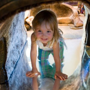 Girl crawling through cave